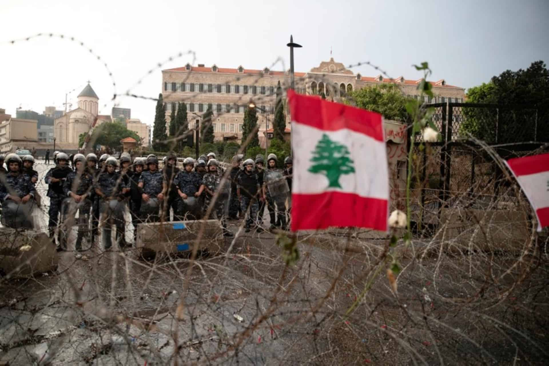 Riot police stand guard behind barbed-wire next to the Government Palace during ongoing anti-government